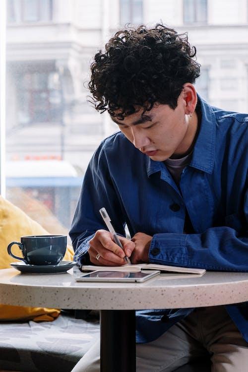 Man in Blue Dress Shirt Writing on White Paper