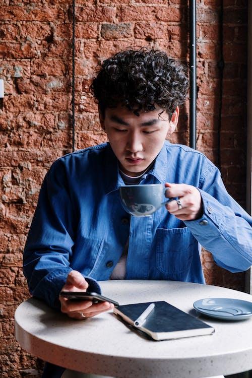 Gratis arkivbilde med arbeidsplass, asiatisk mann, blå skjorte, elektronisk enhet