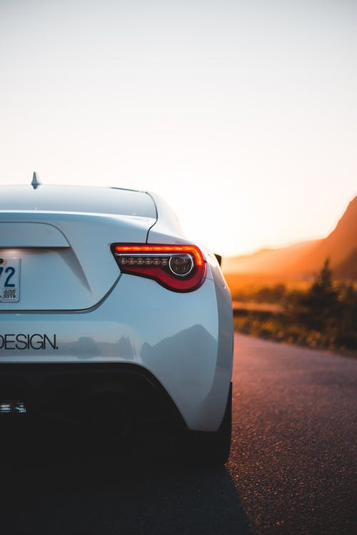 Back detail of white shiny car on smooth asphalt route in back lit of sunset light
