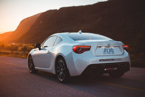 Trendy expensive sport automobile on asphalt route against mountains in valley glowing with sunset light