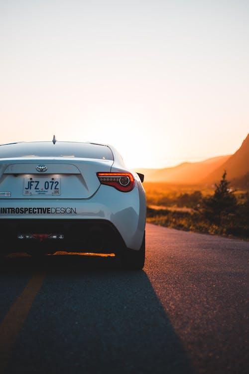 Back part of trendy white car on asphalt roadway in back lit of sundown