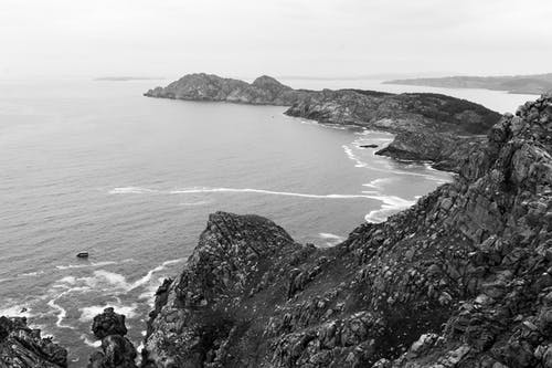 Grayscale Photo of Sea and Mountain