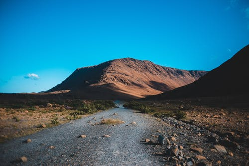 Roadway with scattered stones leading to mountain against blue sky in sunny weather in daylight in summer time in countryside