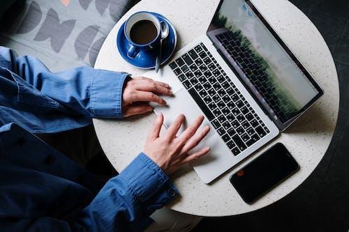 Person in Blue Denim Jeans Using Macbook Pro Beside White Ceramic Mug on White Table