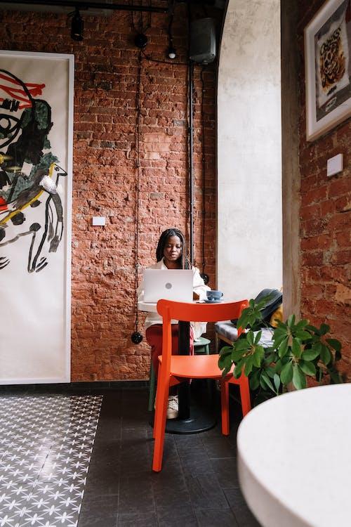 Woman in White Long Sleeve Shirt Sitting on Orange Chair