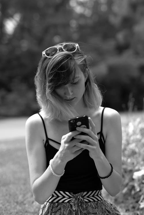 Grayscale Photo of Woman in Tank Top Holding Smartphone