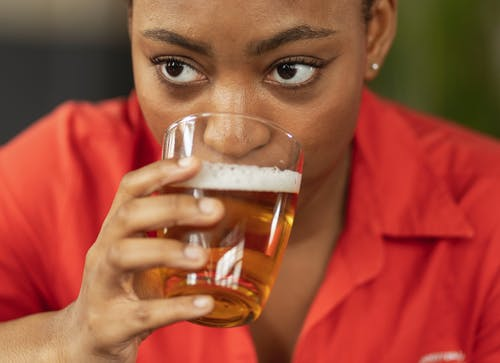 Close Up Photo of Woman in Red Dress Shirt Drinking A Glass of Beer