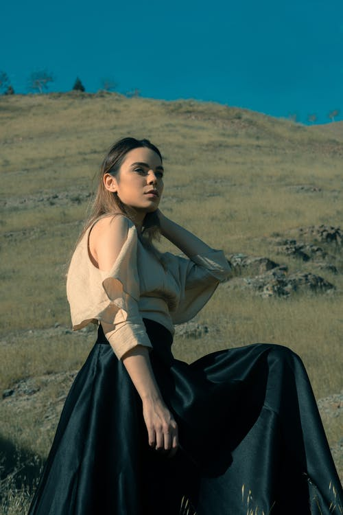 Young female in silky blouse and black satin skirt looking away in grassy slope with rocks