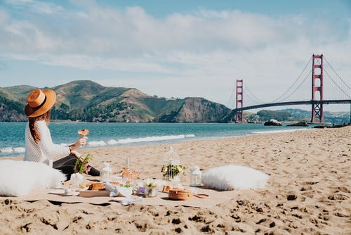 Side view of unrecognizable female traveler in trendy straw hat sitting on sandy beach and drinking wine during picnic near waving sea surrounded by mountains
