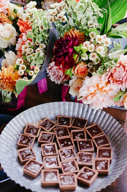 From above of delicious chocolate bars served on plate and placed on tale near aromatic colorful flowers