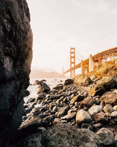 Low angle of suspension bridge crossing river with cliffs on rocky coast against sunset sky