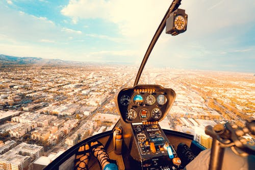 Crop anonymous female traveler sitting in cockpit of modern helicopter and admiring spectacular view of city on sunny day