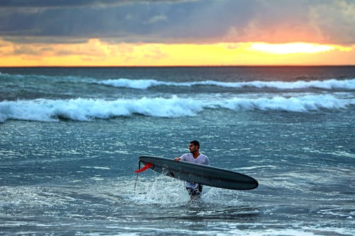 Man in Black Wet Suit Surfing on Sea Waves during Sunset