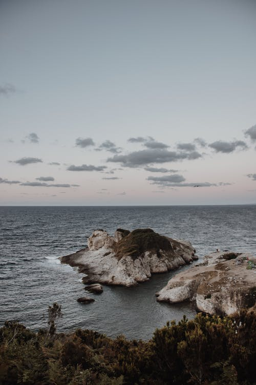 Brown Rock Formation on Sea Under White Clouds