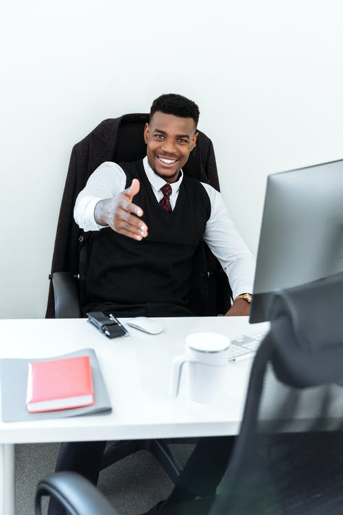 Man in Black Vest Sitting on Black Office Rolling Chair