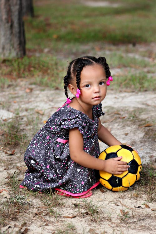 Girl in White Purple and Black Dress Holding Yellow and Black Soccer Ball Outside in Daytime