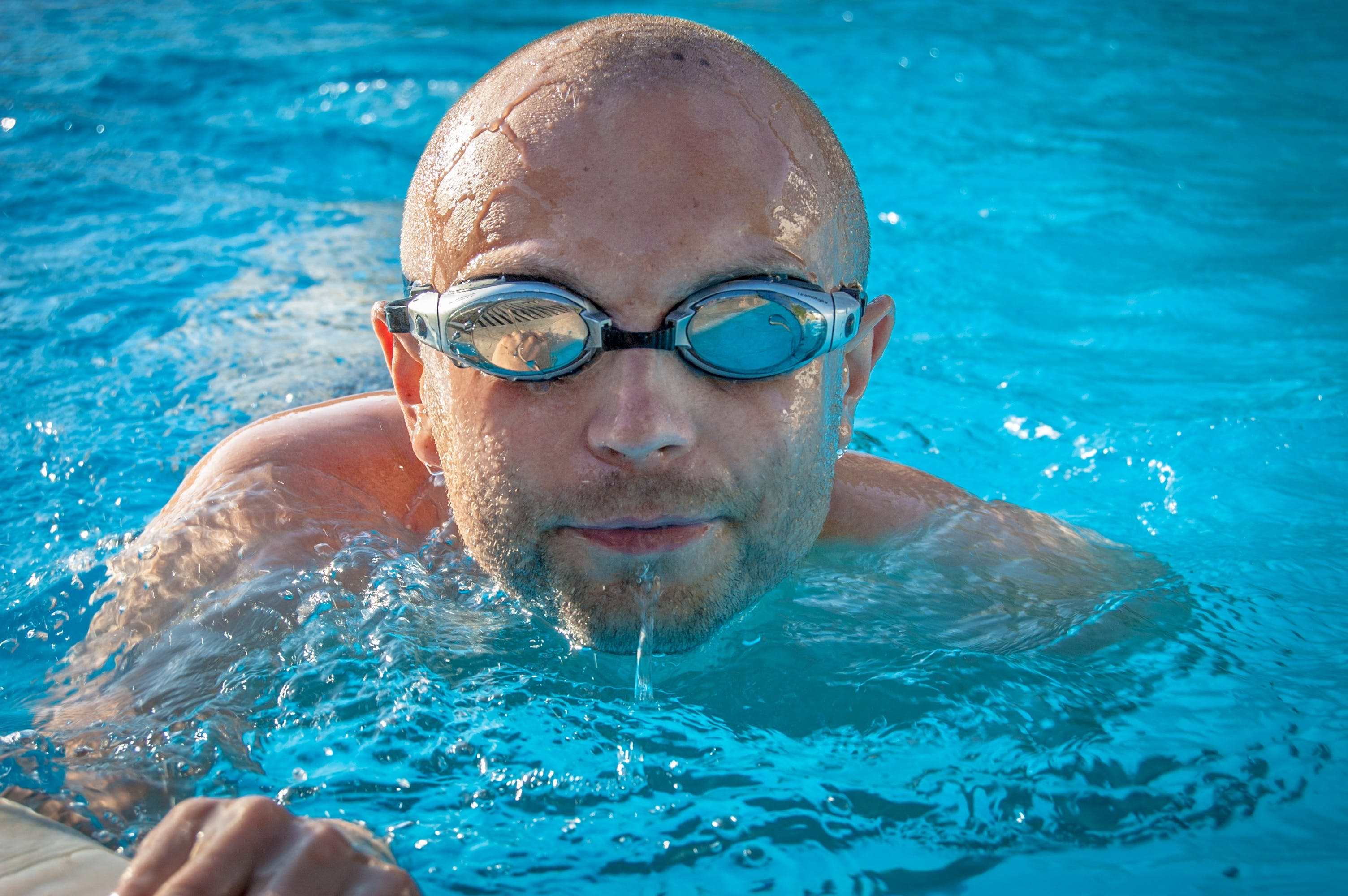 Man With Gray Swimming Goggles in Body of Water