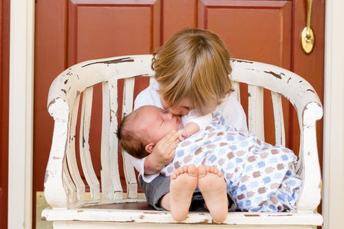 Boy Carrying and Kissing Baby Sitting on Chair