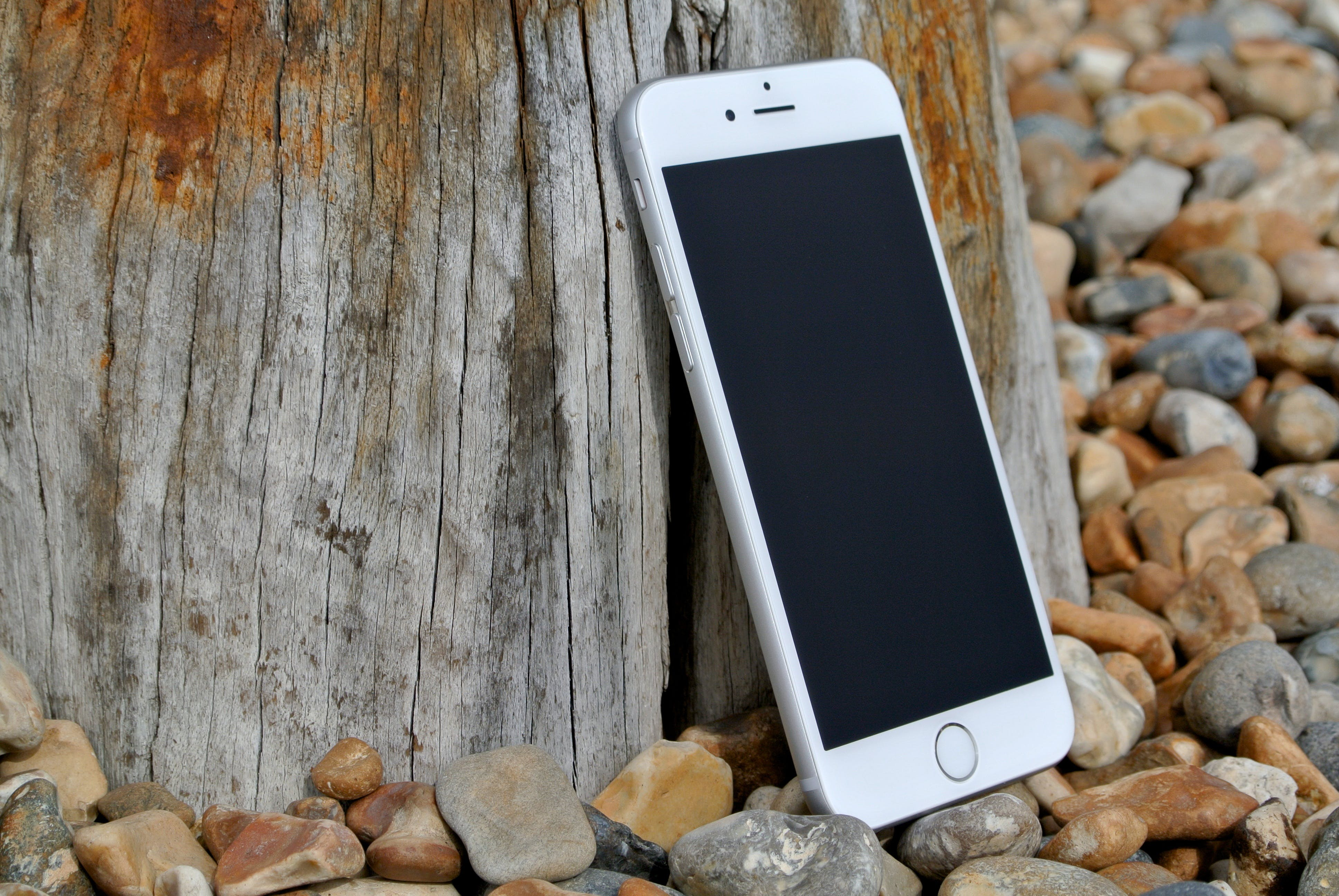 Silver Iphone 6 on Gray and Brown Stone