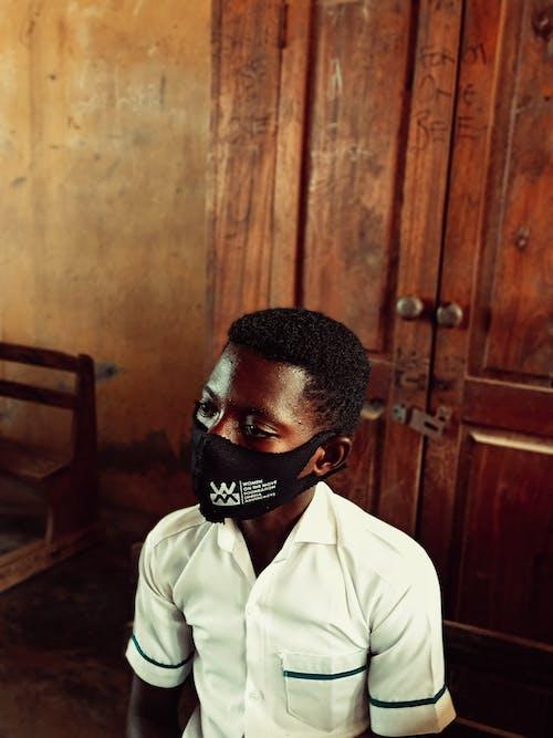 Black boy sitting near wardrobe
