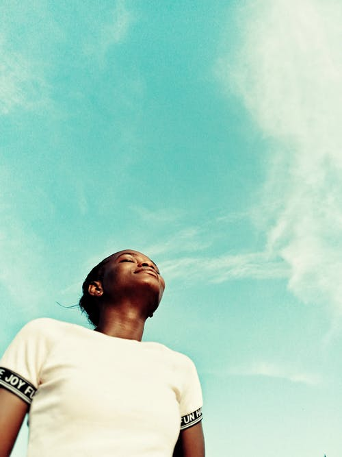 From below of young African American female in white t shirt standing with eyes closed in summer day against blue sky