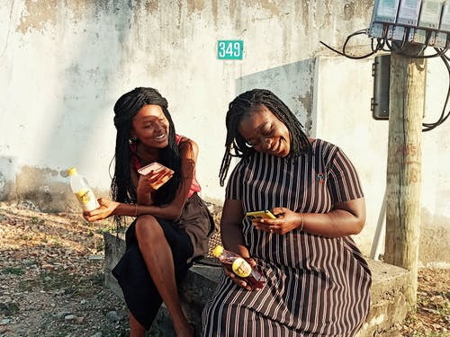 Black women sitting on stone curb