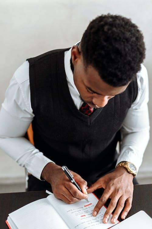 黑色背心和持有黑色智能手機的白色禮服襯衫的男人