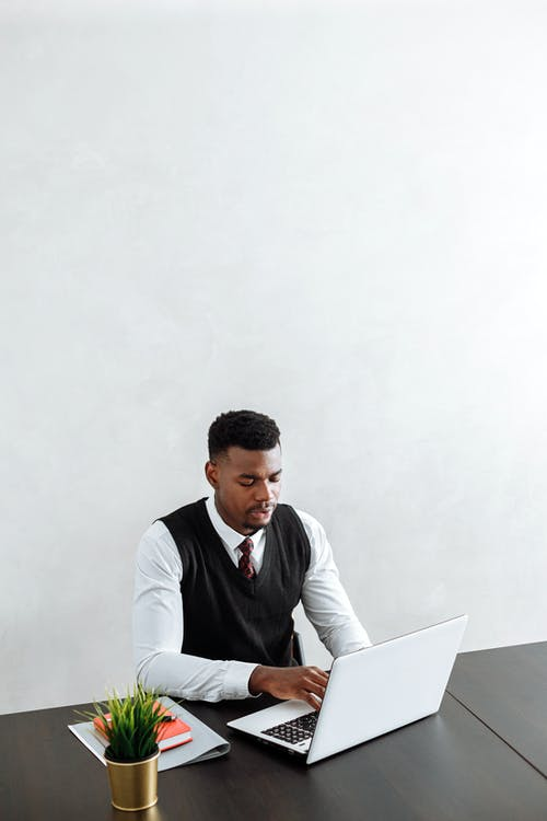 A Man Working with a Laptop in the Office