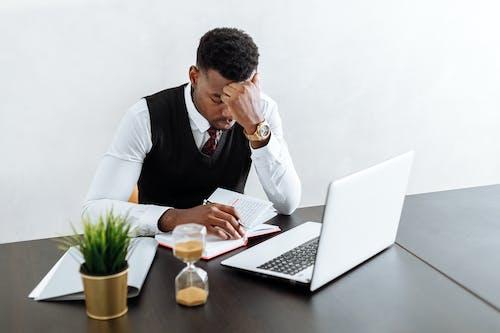 使用macbook Pro的黑色背心和白色正裝襯衫的男人