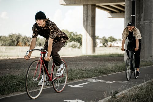 Men Riding Their Bicycles on a Bike Lane