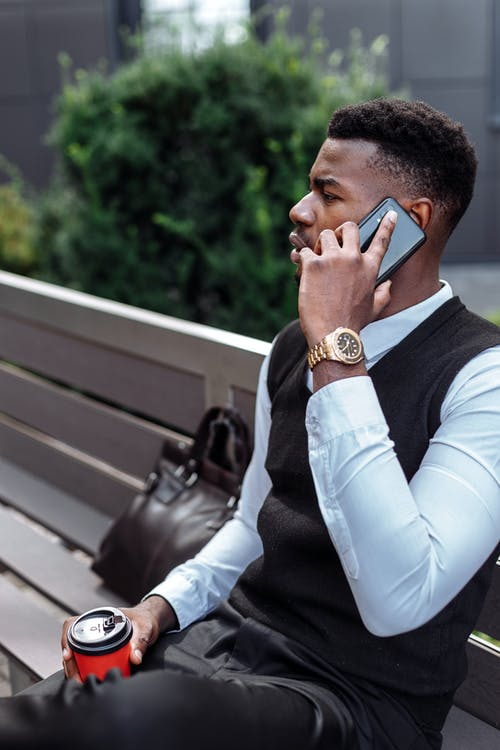A Man Sitting on a Bench While on a Phone Call