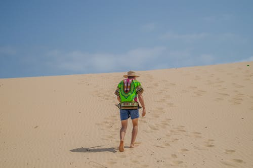 Man in Green Shirt and Blue Denim Shorts Walking on Brown Sand