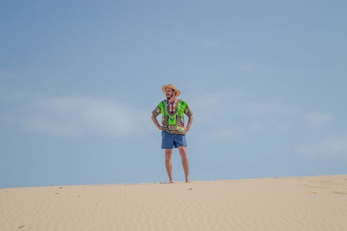 Woman in Green Shirt and Blue Denim Shorts Walking on Brown Sand
