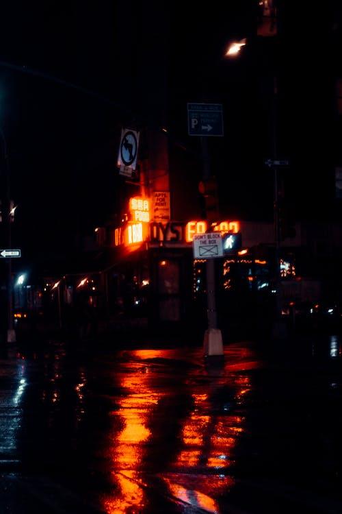 Building with shiny inscriptions illuminating road at night