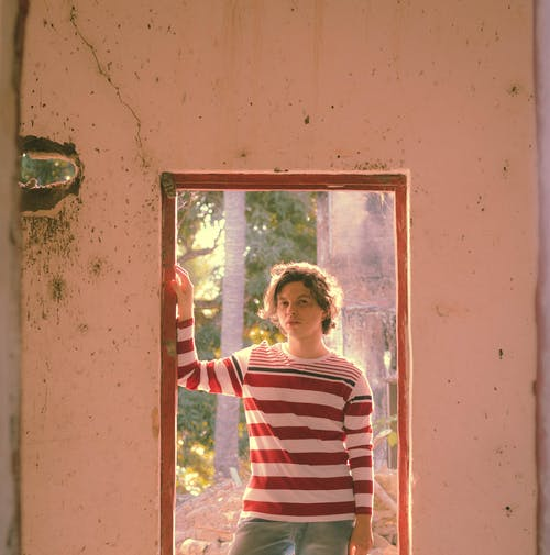 Male teen in trendy striped apparel looking at camera while standing in aged house in sunlight in back lit