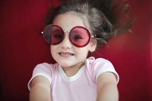 Girl in White Crew Neck T-shirt Wearing Red Framed Sunglasses