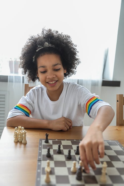 Happy black girl moving figurines on chess board