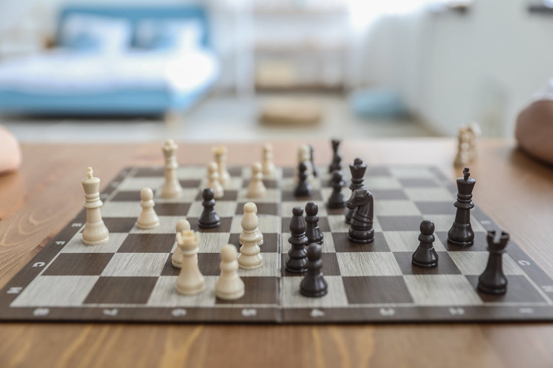 Small white and black figurines on thin square chess board in bedroom in daytime on blurred background