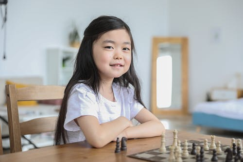 Asian girl playing chess in bright room