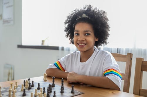 Black girl playing chess at table in room