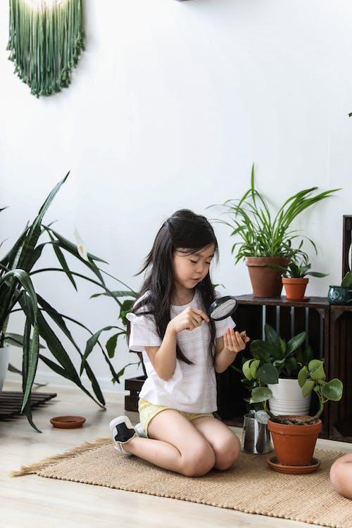 Linda Chica Asiática Investigando Hojas De Plantas En Macetas