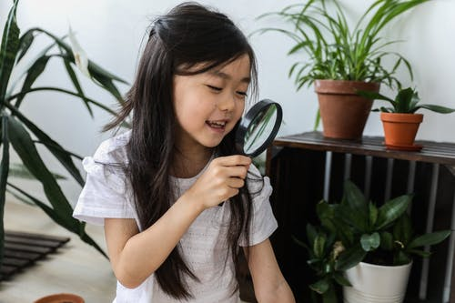 Little happy cute Asian girl looking at magnifier