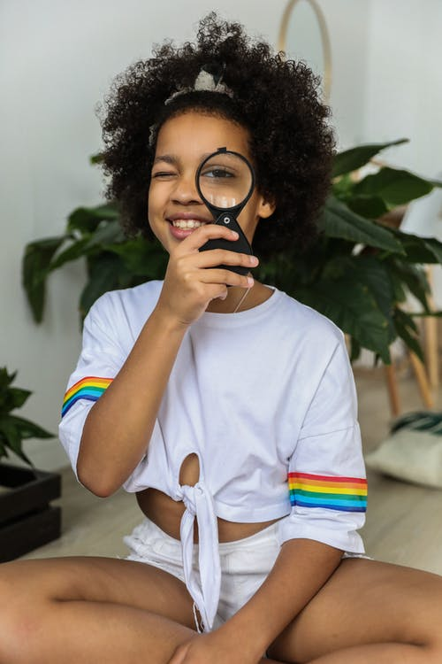 Black girl smiling and looking through magnifier