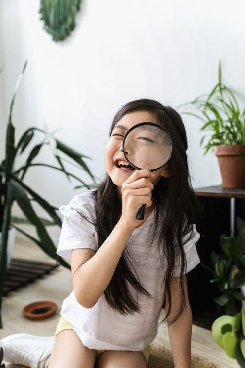 Funny Asian girl looking through magnifier