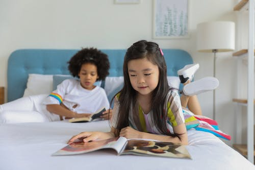 Diverse girls resting on bed and looking through magazine