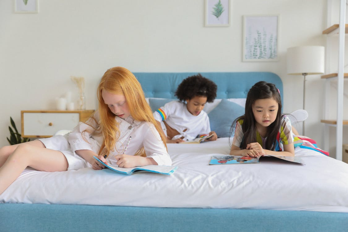 Multiethnic cute girls reading journals on spacious bed
