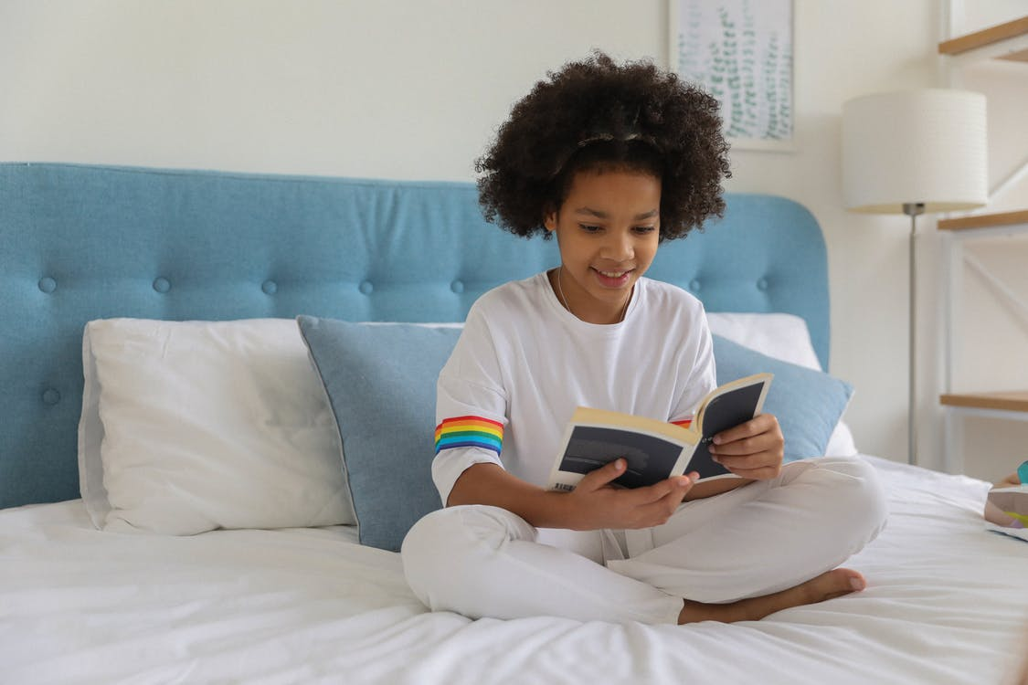 Black girl reading book on bed