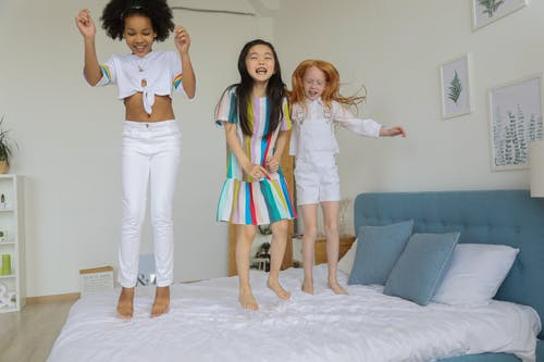 Full body of cheerful multiracial girls laughing and smiling while jumping on bed in modern comfortable room