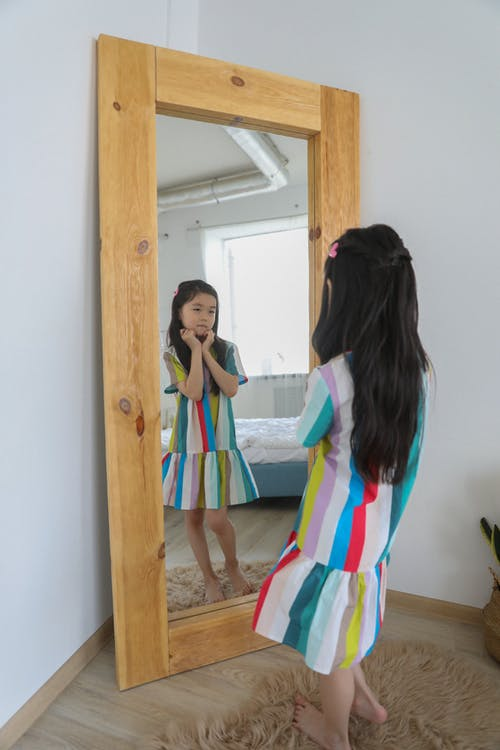 Asian girl admiring in mirror with wooden frame