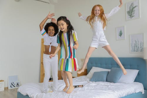 Full body of cute positive little girls smiling and jumping on cozy bed in modern room